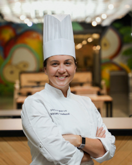 Woman smiling wearing chef coat and hat