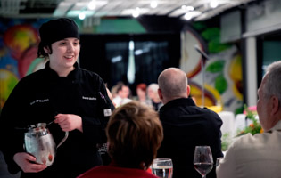 Female culinary student speaking with guests at an event
